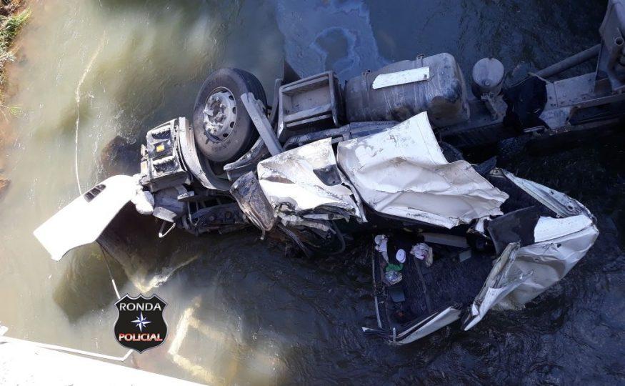 Caminhoneiro fica preso às ferragens ao capotar de ponte e cair em rio