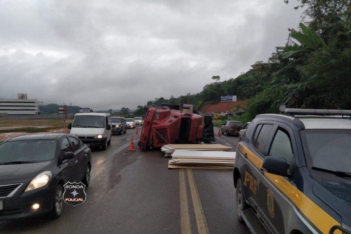 Caminhão carregado com chapas de compensado tomba e deixa trânsito lento na 470