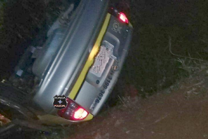 Carro de autoescola capota a margem de rodovia durante a madrugada