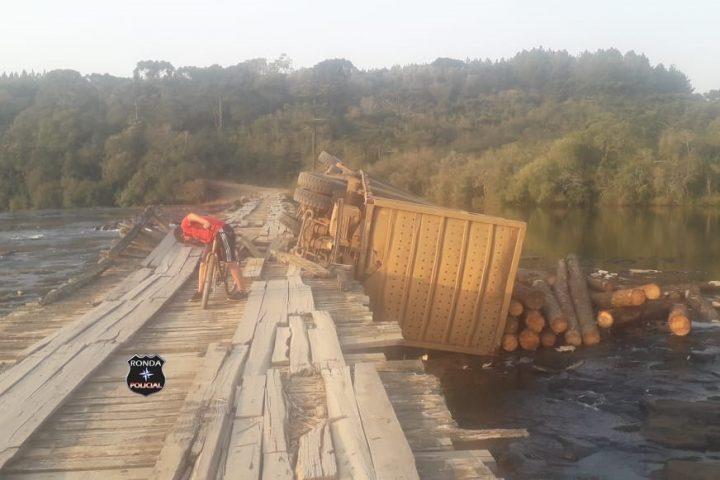 Caminhão carregado de toras tomba de ponte no interior de Passos Maia