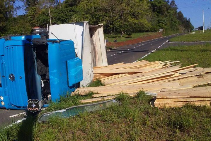 Caminhão carregado com madeira tomba em rodovia