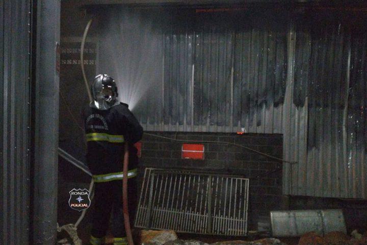Incêndio de grandes proporções consome completamente estrutura de oficina mecânica durante a noite